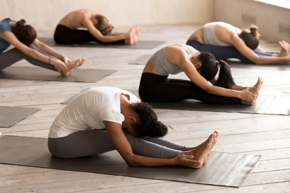Yoga group practicing Sitting Forward Bend (Paschimottanasana)